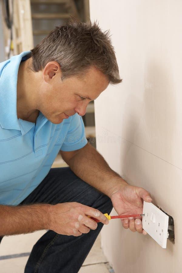 安装插口墙壁的电工 免版税库存照片
