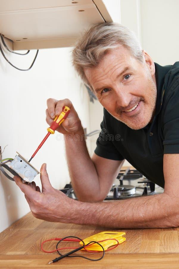 安装插口的电工在新房 免版税图库摄影
