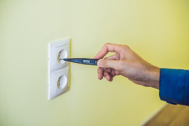 安装插口的电工在新房 免版税库存照片