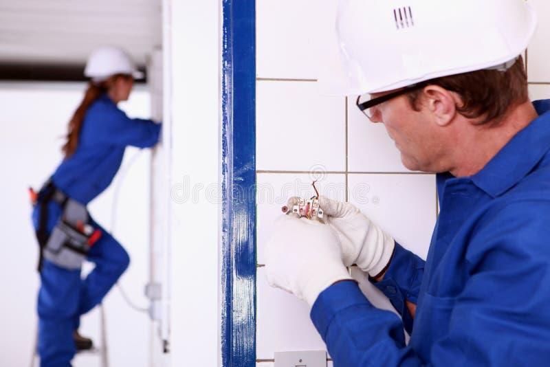 安装插口的电工 免版税库存照片