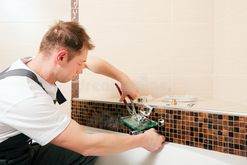 安装搅拌机管道工轻拍的卫生间 库存照片