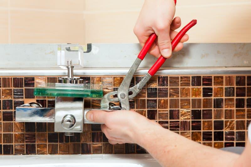 安装搅拌机管道工轻拍的卫生间 库存图片