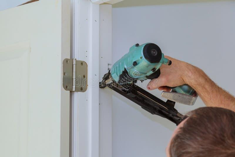 安装新的内门,特写镜头球状木匠的手对负 图库摄影