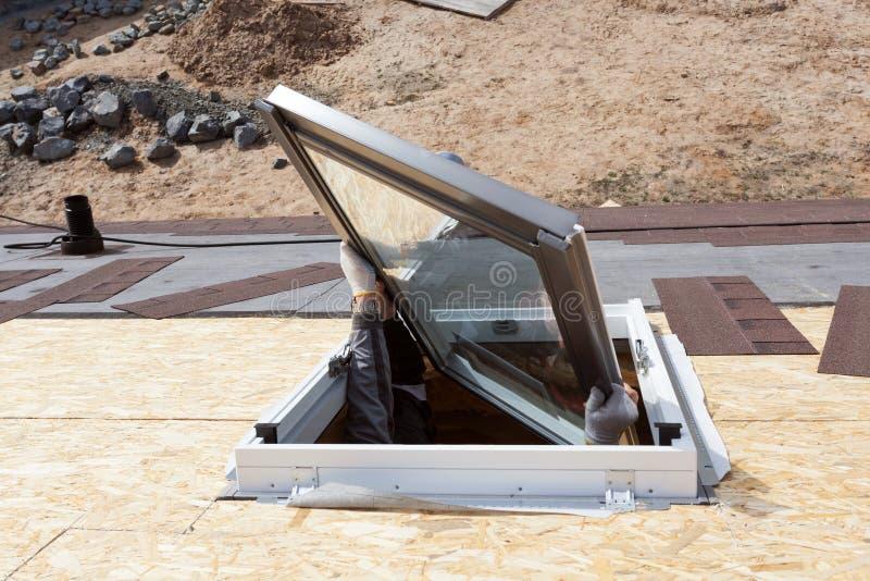 安装新的塑料有双重斜坡屋顶的房屋或天窗窗口的沥青木瓦屋顶的工作者 库存照片