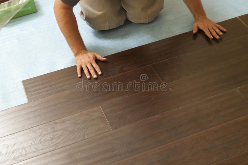 安装新的层压制品的木地板的人 库存图片