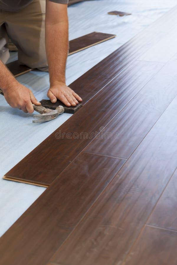 安装新的层压制品的木地板的人 图库摄影
