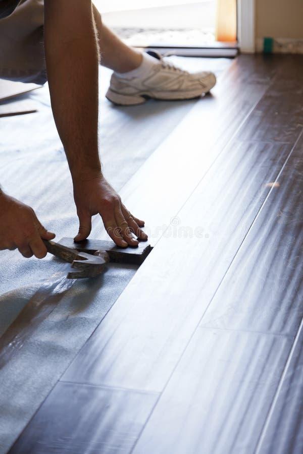 安装新的层压制品的木地板的人 免版税库存照片
