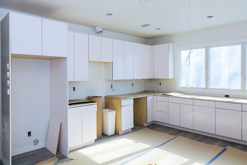 安装新的归纳滚刀在现代厨房厨房设施厨柜 免版税库存照片