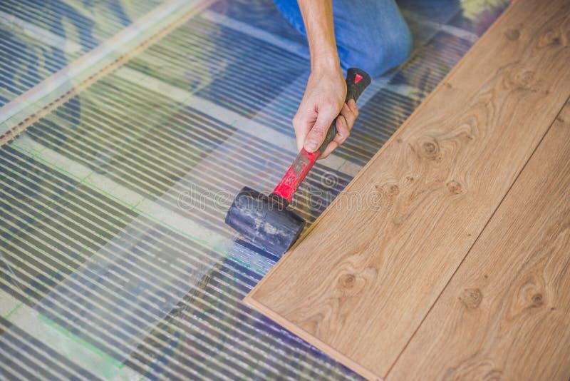 安装新的木层压制品的地板的人 在层压制品的地板下的红外地板采暖系统 免版税库存图片