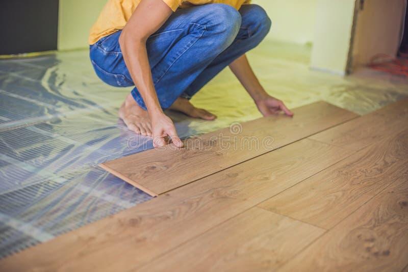 安装新的木层压制品的地板的人 红外地板热 免版税库存图片