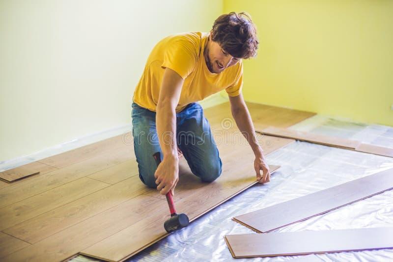 安装新的木层压制品的地板的人 红外地板热 免版税库存照片