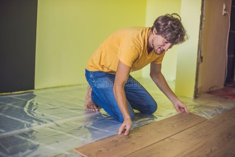 安装新的木层压制品的地板的人 红外地板热 图库摄影