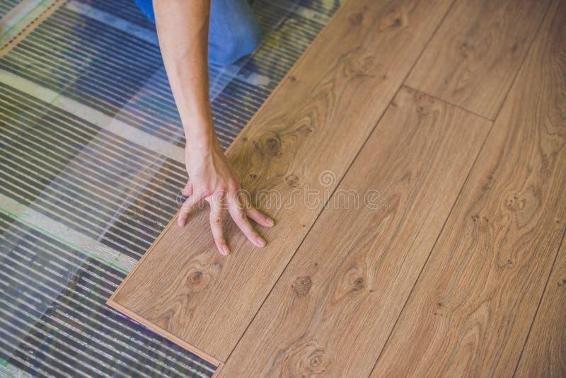 安装新的木层压制品的地板的人 红外地板热 库存图片