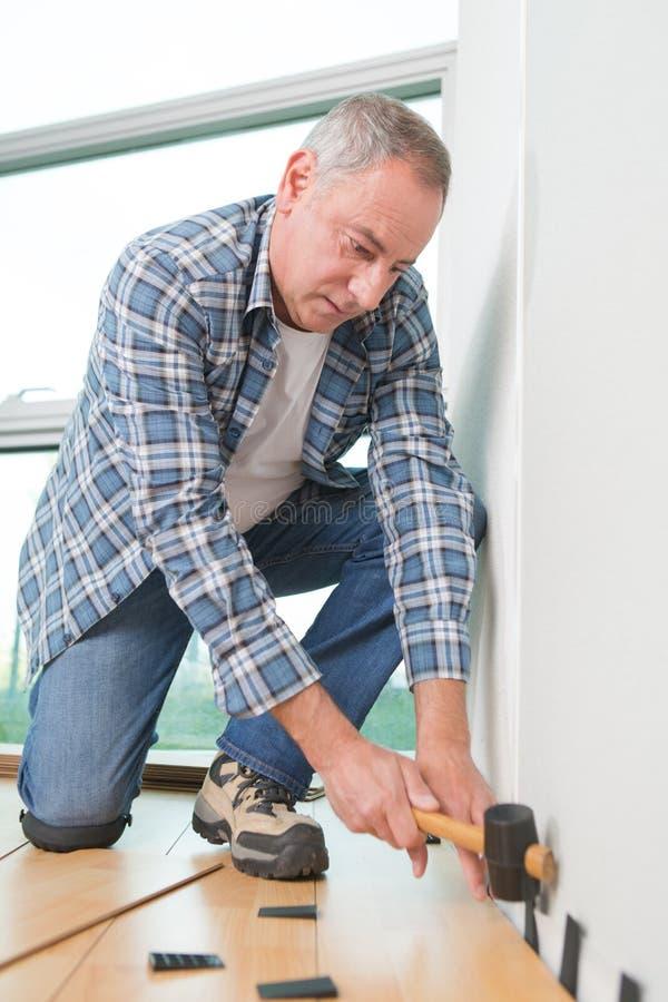 安装新的木层压制品的地板的人 免版税库存图片