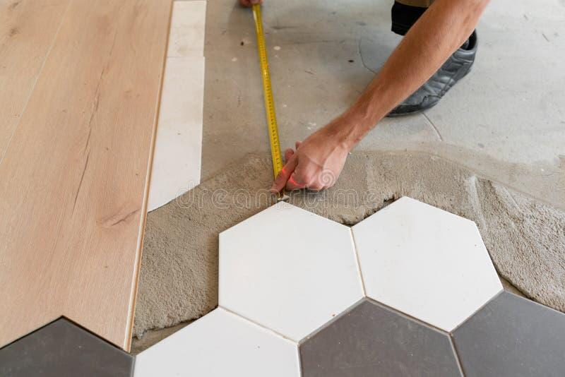 安装新的木层压制品的地板的男性工作者在一个温暖的影片地板 楼层热化红外线下层压制品系统 免版税库存图片