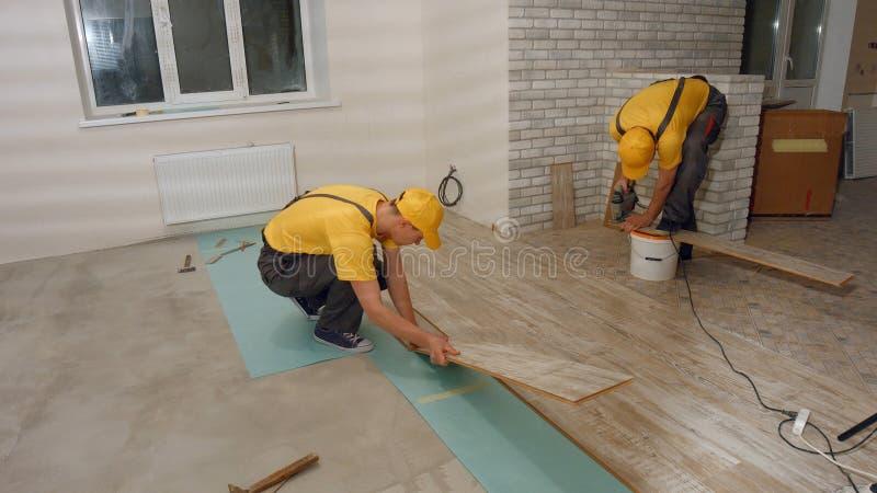 安装新的木层压制品的地板的男性工作者 免版税库存图片
