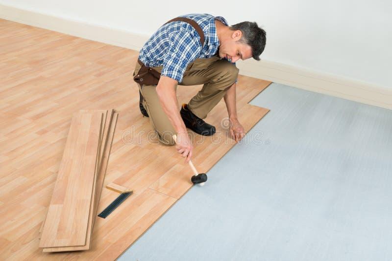 安装新的被碾压的木地板的人 库存照片