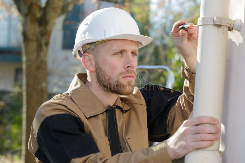 安装新的阀门的水管工在管子房子外 免版税图库摄影