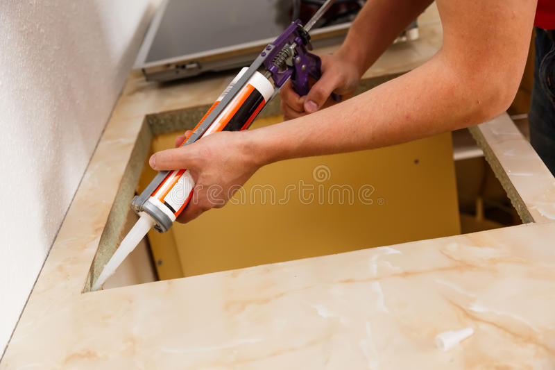 安装新的滚刀在现代厨房 免版税库存图片