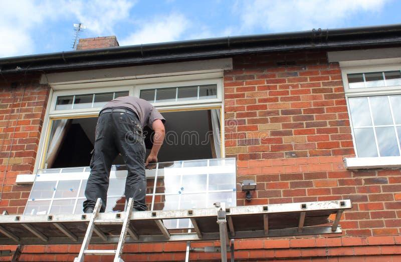 安装新的玻璃的窗口钳工 免版税库存照片