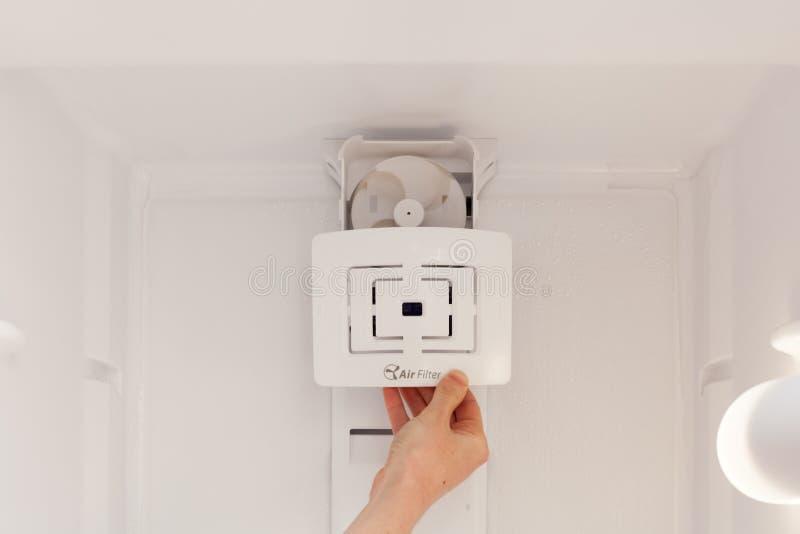 安装新,清洗在一个空的被洗涤的冰箱的空气过滤器 少妇清洁冰箱 免版税库存照片