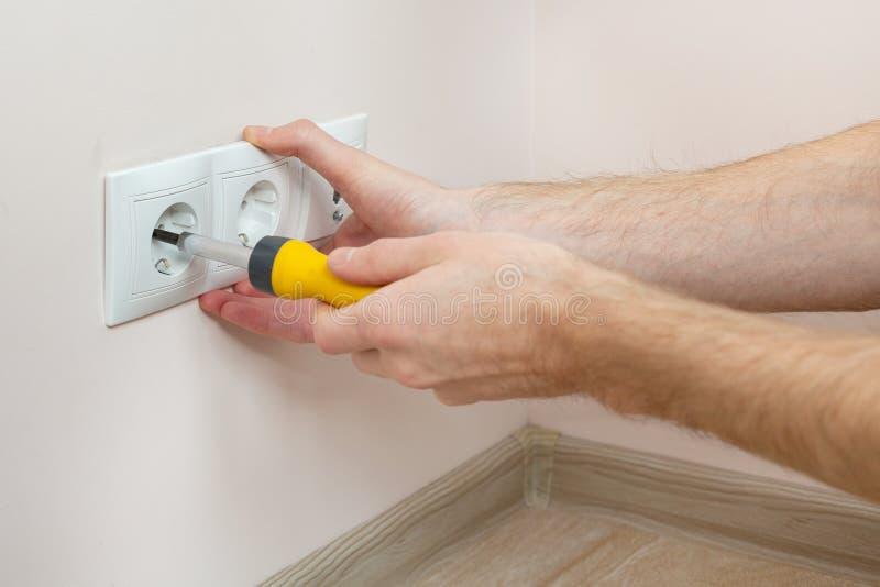 安装有螺丝刀的电工的手墙壁电源插座 免版税库存照片