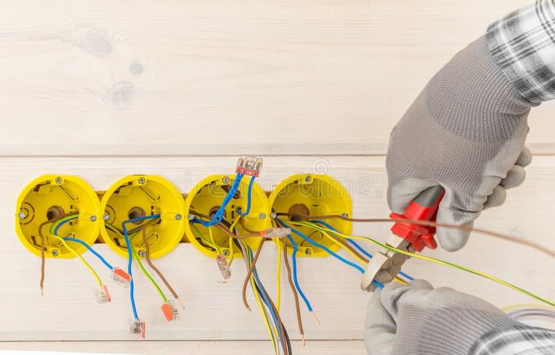安装有螺丝刀的电工的手电子插口在墙壁 免版税库存照片