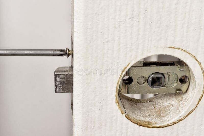 安装有螺丝刀的门闩在门 免版税库存图片