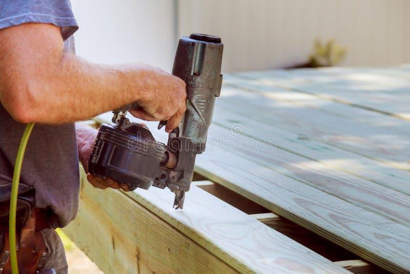 安装木地板室外大阳台的英俊的人木匠在新房 免版税库存图片