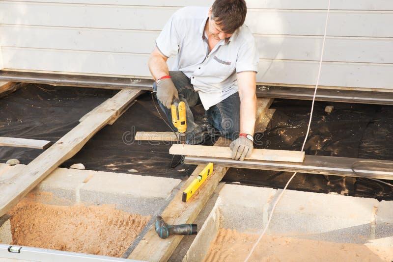 安装木地板室外大阳台的英俊的年轻人木匠在新房建造场所 免版税库存图片