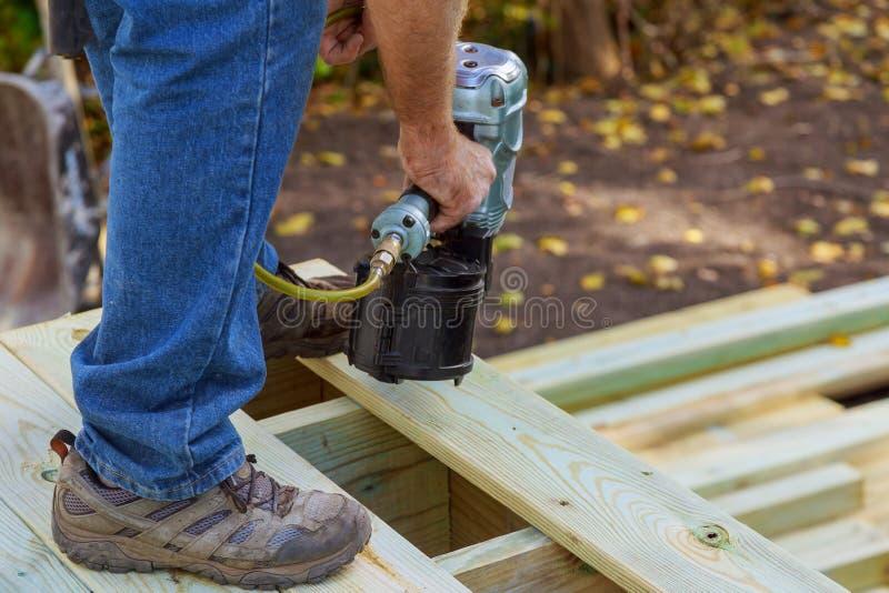 安装木地板的杂物工在露台,运作使用钉子枪钉牢 库存照片