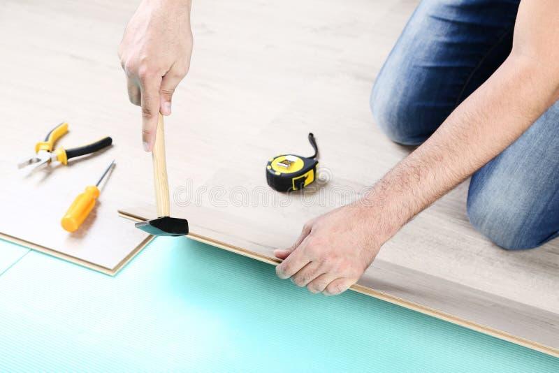 安装木材层压制品的地板的人 免版税库存照片