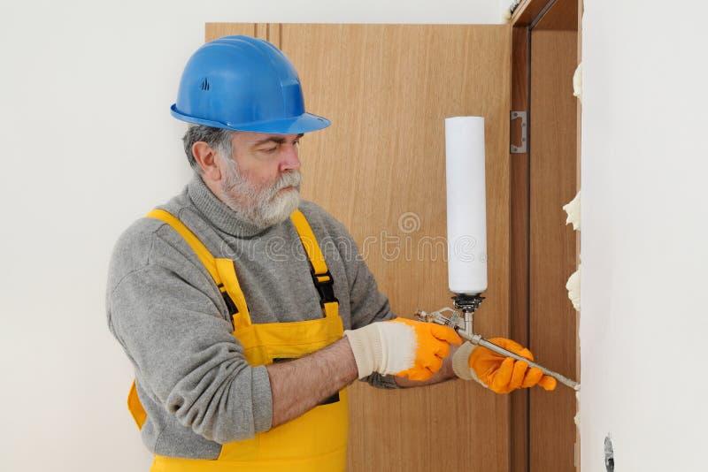 安装木门的工作者,使用聚氨酯泡沫体 库存图片