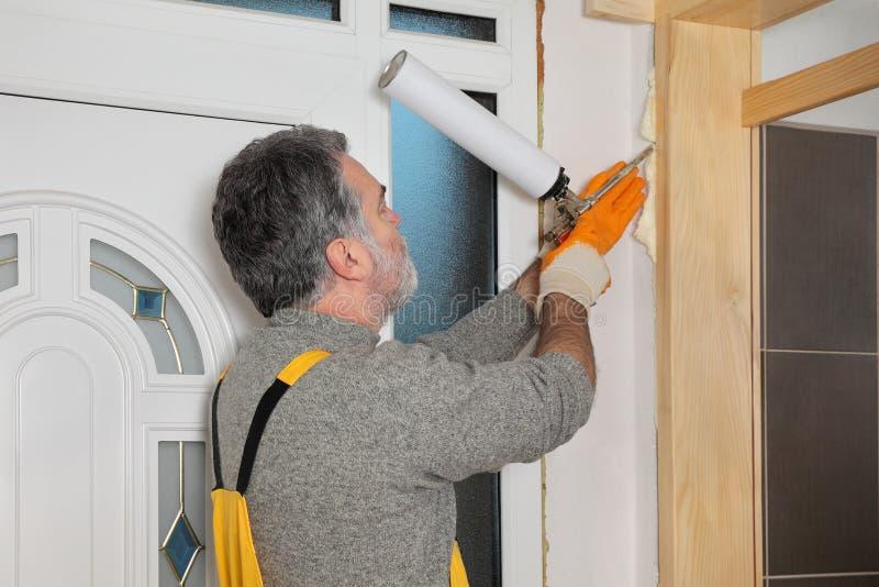 安装木门的工作者,使用聚氨酯泡沫体 库存照片