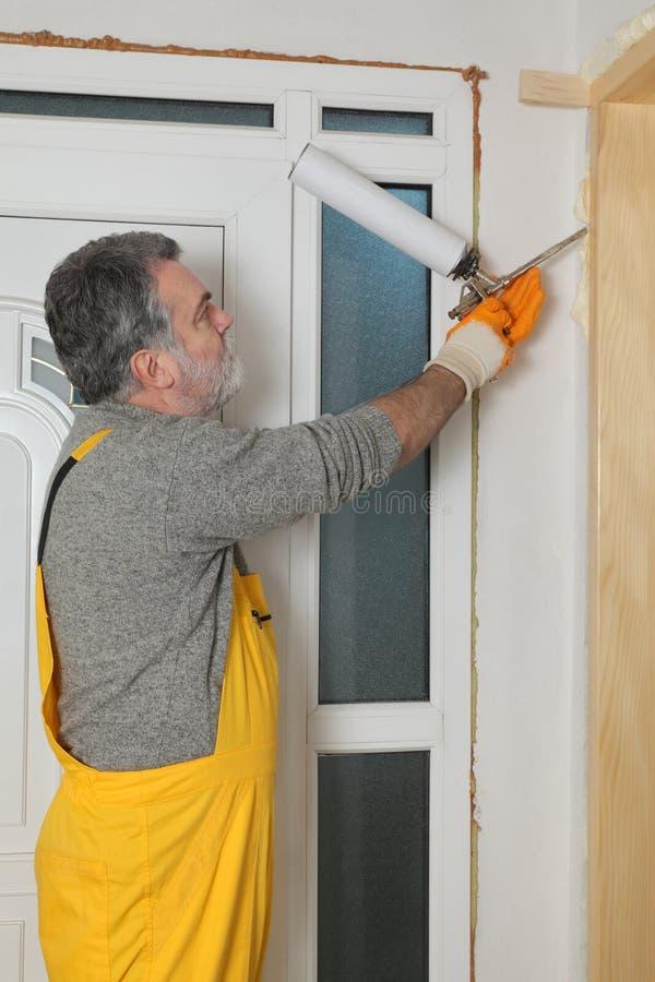 安装木门的工作者,使用聚氨酯泡沫体 免版税图库摄影