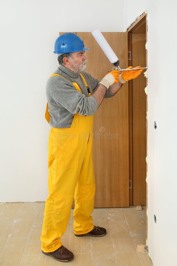 安装木门的工作者,使用聚氨酯泡沫体 免版税库存照片