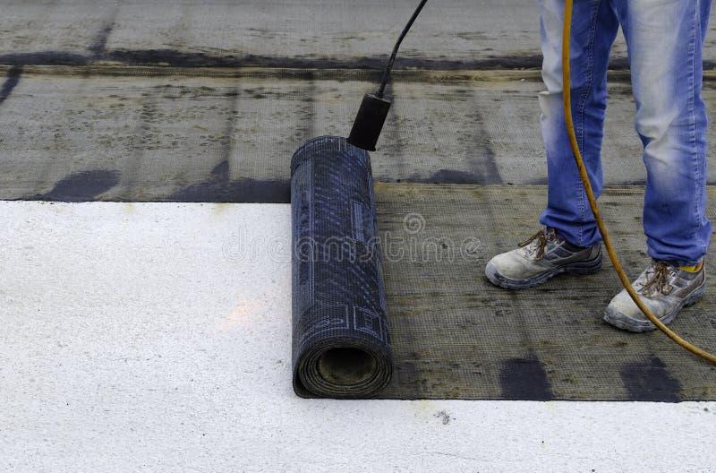 安装沥青防水的膜的卷防水的盖屋顶的人 库存照片