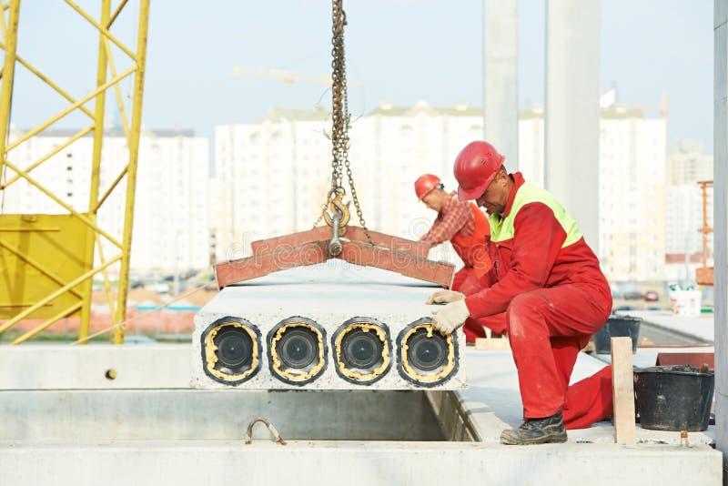 安装混凝土板的建造者工作者 免版税库存图片