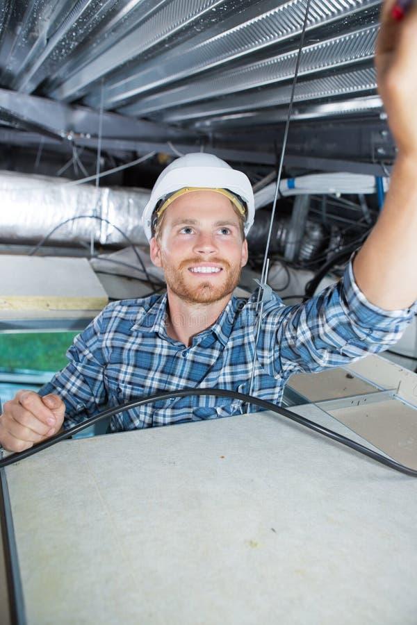 安装烟检测器的工作者在天花板 免版税库存照片