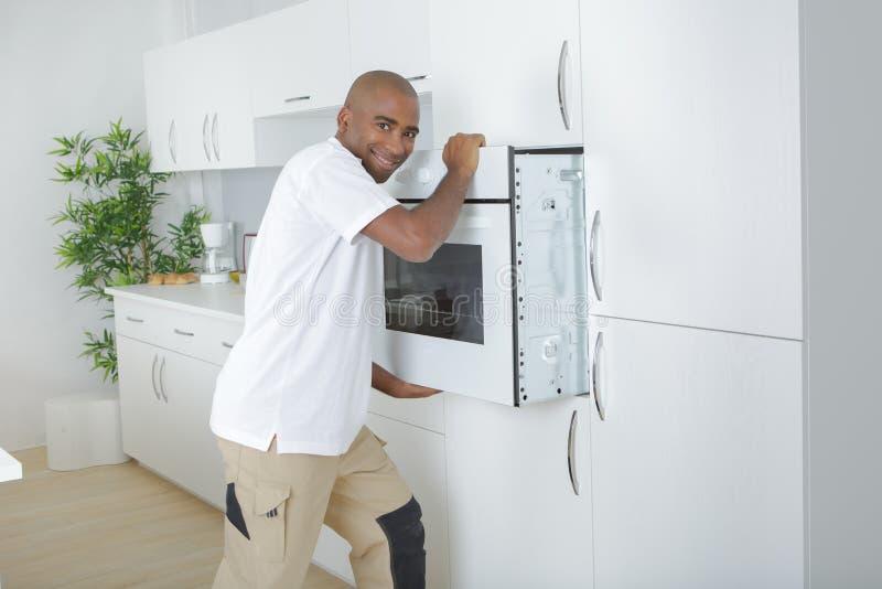 安装现代固定烤箱的工作者在厨房 库存照片
