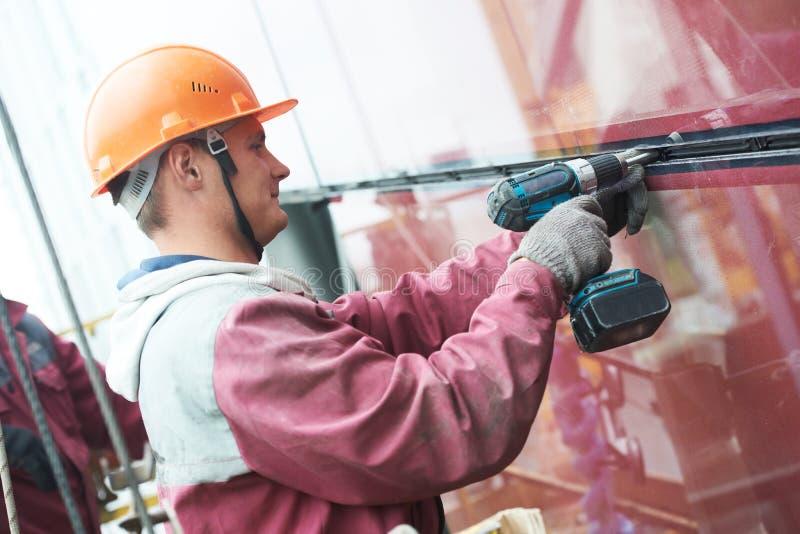 安装玻璃窗的工作者在大厦 免版税库存图片
