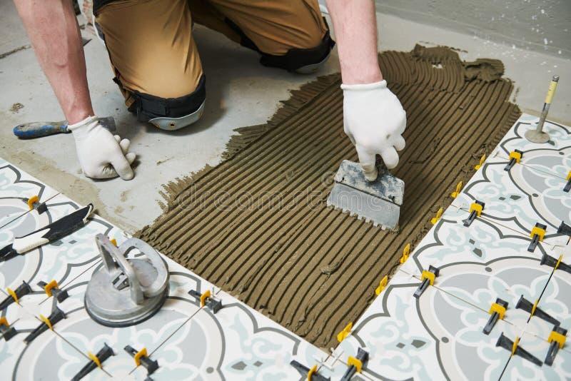 安装瓦片的铺磁砖工在卫生间地板 在家户内整修 库存照片