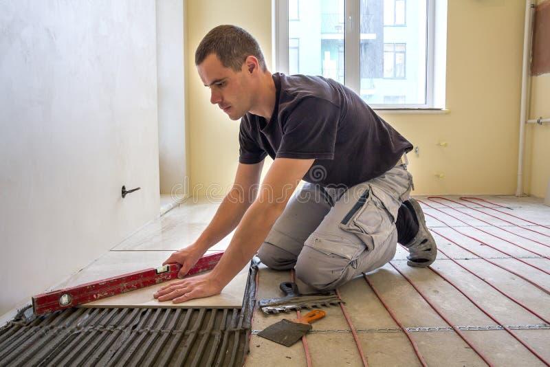 安装瓷砖的年轻工人铺磁砖工使用杠杆在与热化红色电缆导线系统的水泥地板 ? 免版税库存图片