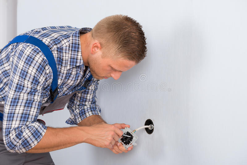 安装电子插口的电工 免版税库存照片