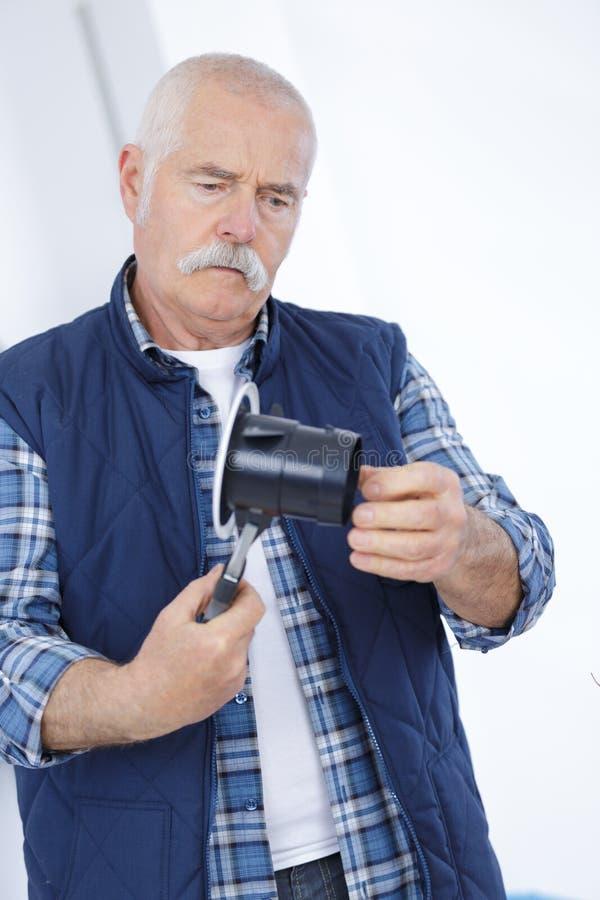 安装电阀门的资深工作者 库存照片