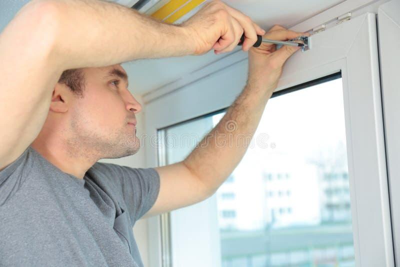 安装百叶窗的年轻人 免版税图库摄影