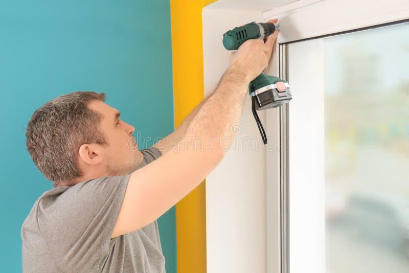安装百叶窗的年轻人 免版税库存照片