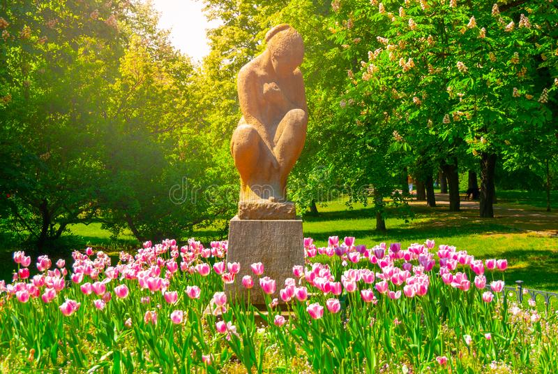 安装的妇女雕塑在Letna公园在与桃红色郁金香的晴朗的夏日,布拉格,捷克 免版税库存照片