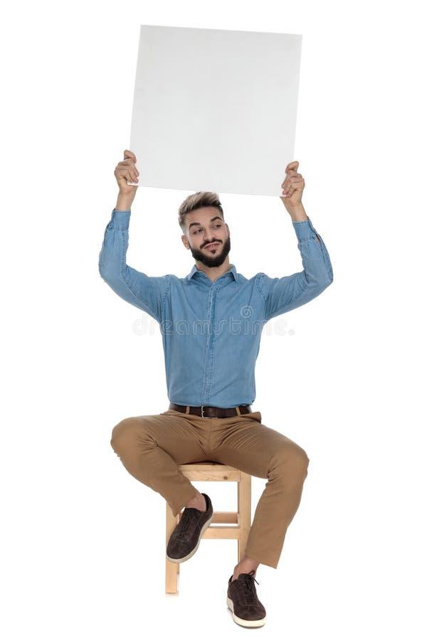 安装的愚笨的人在天空中拿着空的广告牌 免版税库存图片