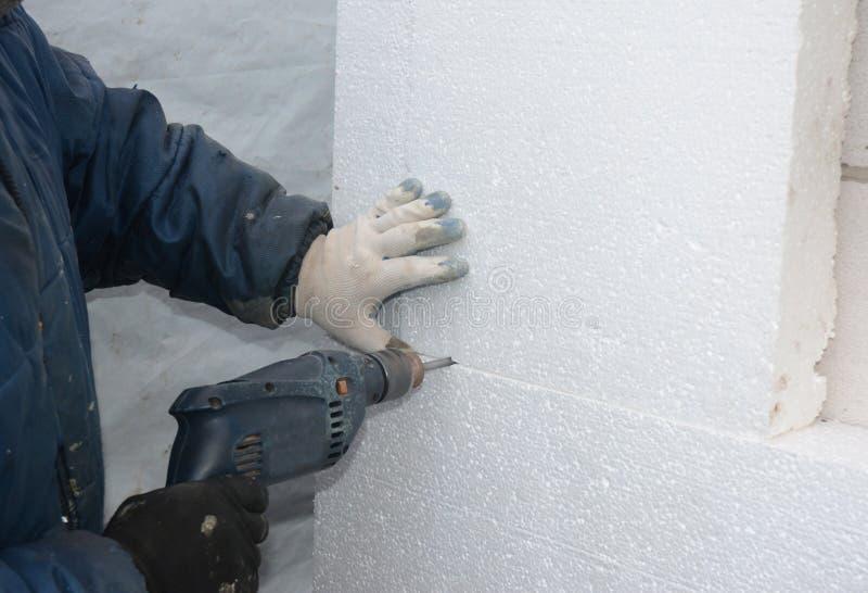 安装的船锚建造者钻墙壁拿着刚性绝缘材料泡沫板 库存照片
